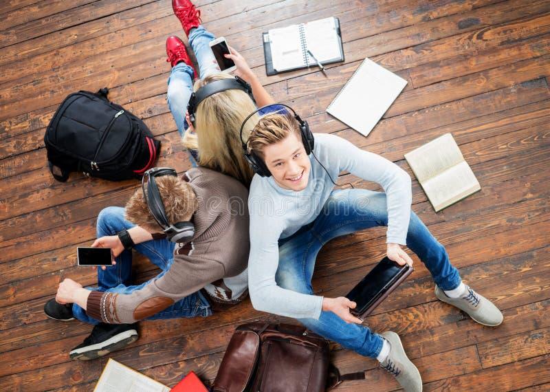 使用智能手机的小组学生 免版税库存照片