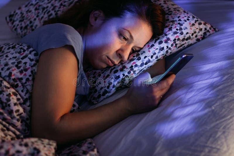 使用智能手机的少妇在床在晚上 免版税图库摄影
