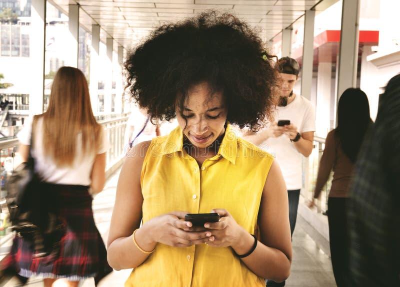 使用智能手机的少妇在走的乌鸦中间 库存图片