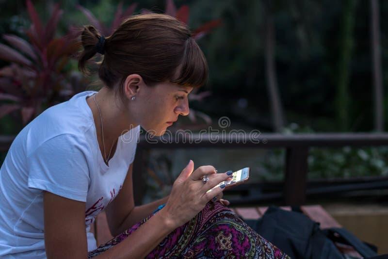 使用智能手机的少妇户外在夜间 巴厘岛 库存图片
