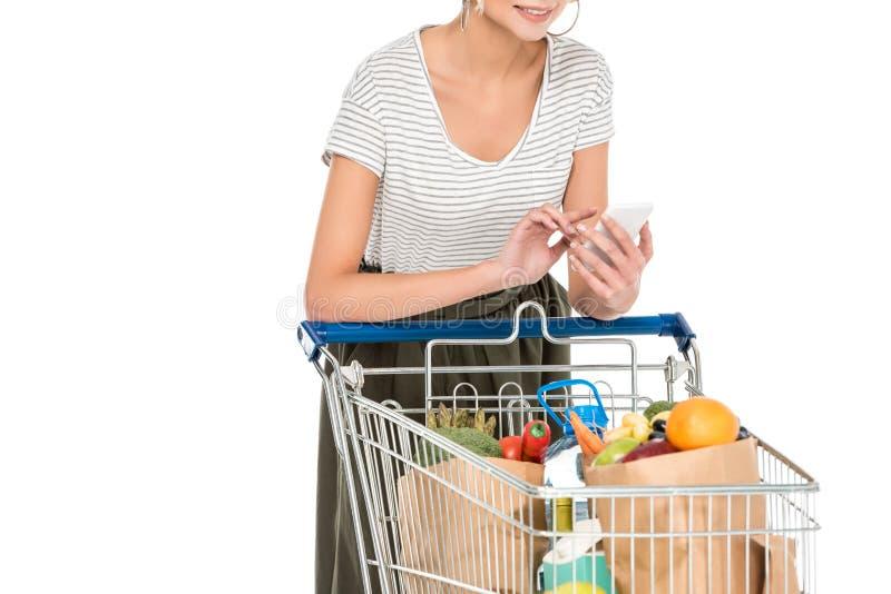 使用智能手机的少妇播种的射击,当倾斜在有食品杂货袋的时购物的台车 免版税图库摄影