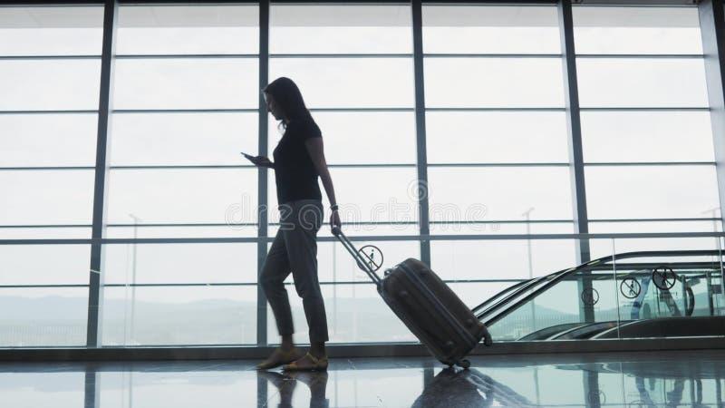 使用智能手机的年轻俏丽的女实业家在机场,当等她的队列注册,旅行的概念时 库存图片