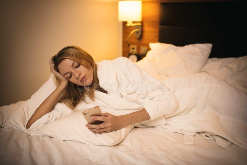 使用智能手机的年轻女人 说谎在床上 免版税库存图片