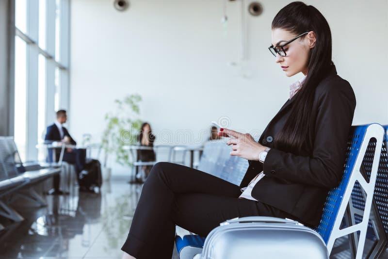 使用智能手机的年轻女实业家在离开休息室 免版税库存照片