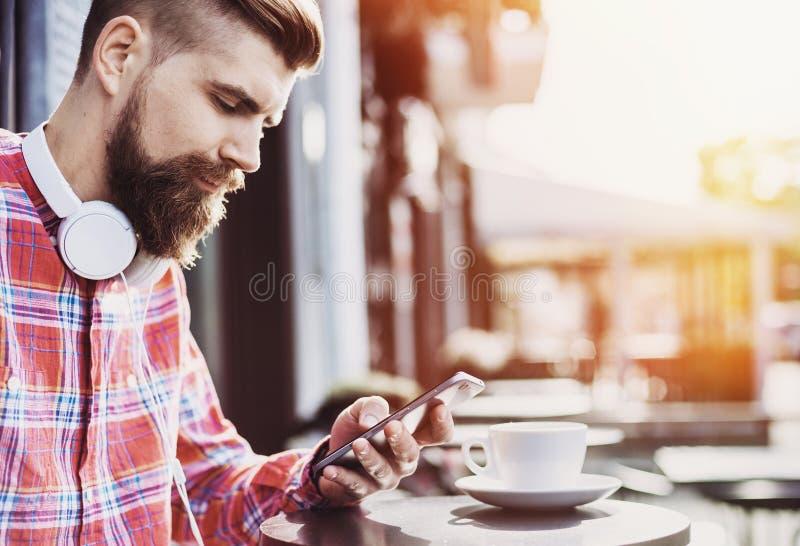 使用智能手机的年轻快乐的人在城市 关闭快乐的成人使用手机在咖啡馆 库存图片