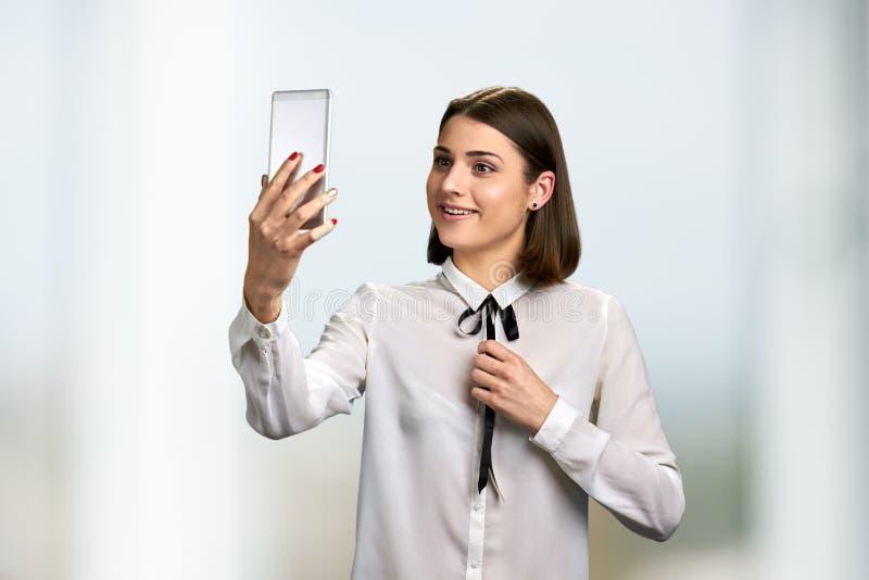 使用智能手机的年轻快乐的妇女 库存图片