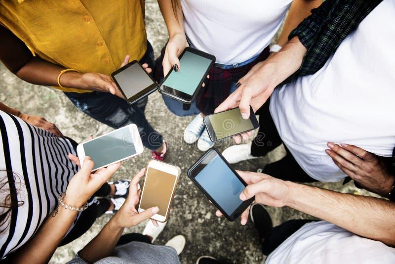 使用智能手机的年轻成人在圈子社会媒介和连接概念 库存照片