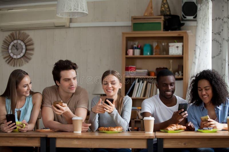 使用智能手机的微笑的不同的年轻女人和人在咖啡馆 库存照片