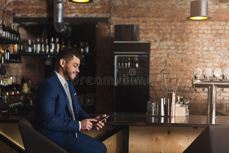 使用智能手机的微笑的商人在酒吧 免版税图库摄影