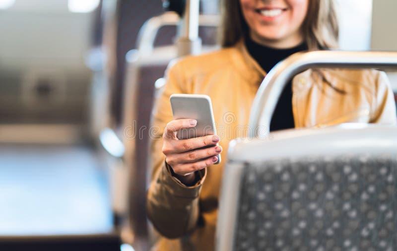 使用智能手机的微笑的妇女在火车、地铁、公共汽车或者电车 库存照片