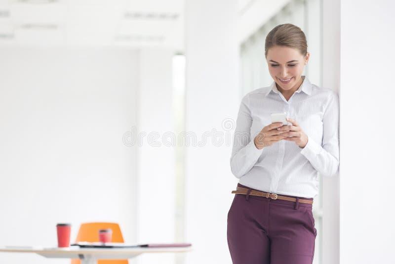 使用智能手机的微笑的年轻女实业家,当站立在新的办公室时 图库摄影