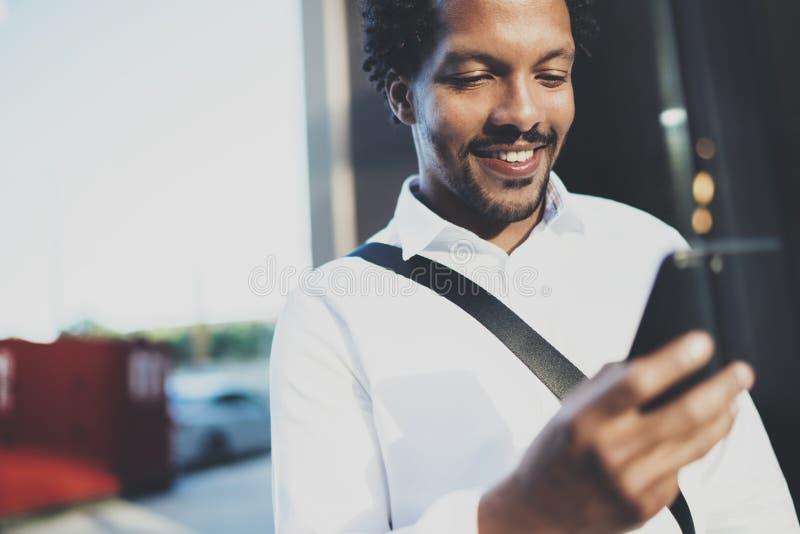 使用智能手机的微笑的美国非洲人特写镜头画象对正文消息朋友在晴朗的街道 概念  免版税图库摄影