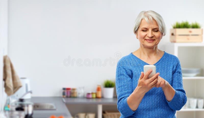 使用智能手机的微笑的资深妇女在厨房 免版税库存照片