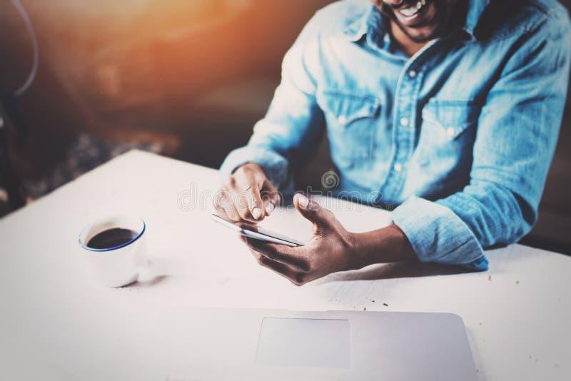 使用智能手机的微笑的年轻非洲人,当坐在木桌他的现代家时 人工作的概念 免版税库存图片