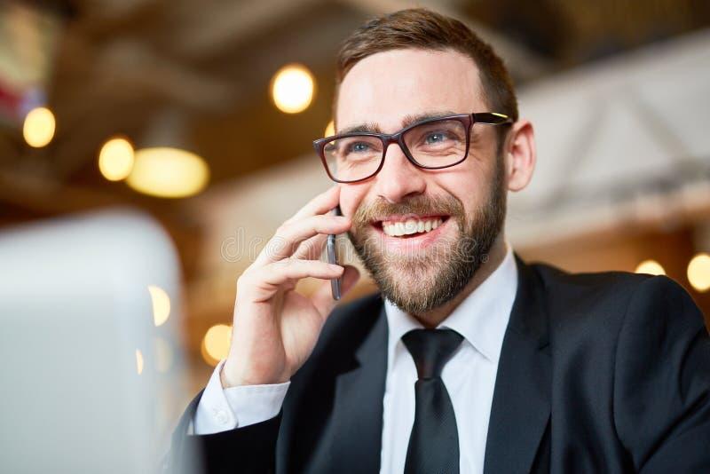 使用智能手机的快乐的商人 免版税库存图片