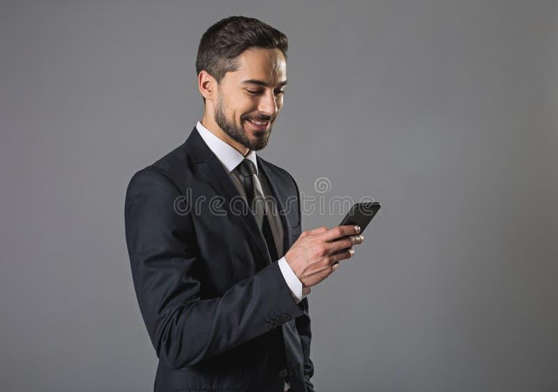 使用智能手机的快乐的微笑的有胡子的人 免版税库存照片