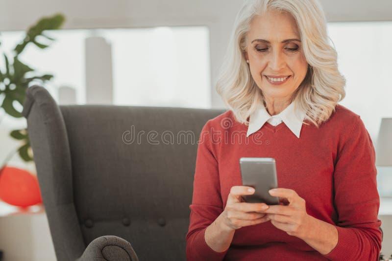 使用智能手机的快乐的资深妇女画象  免版税库存图片