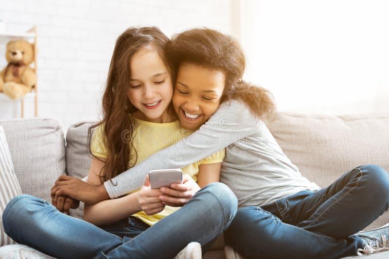 使用智能手机的愉快的女孩和在家拥抱 免版税图库摄影