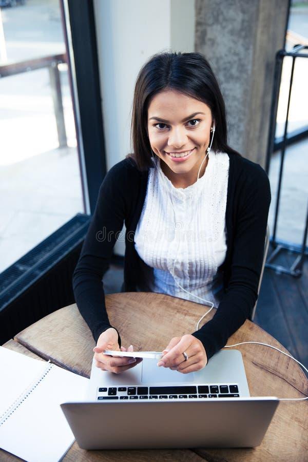 使用智能手机的愉快的女实业家在咖啡馆 免版税库存图片