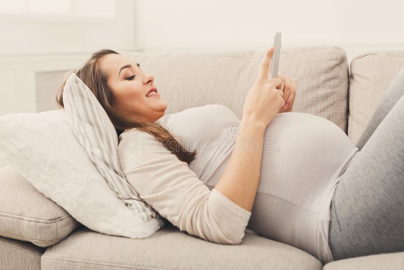使用智能手机的愉快的孕妇 免版税库存图片
