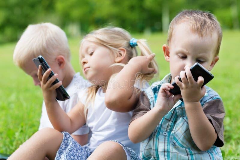 使用智能手机的愉快的孩子 免版税图库摄影