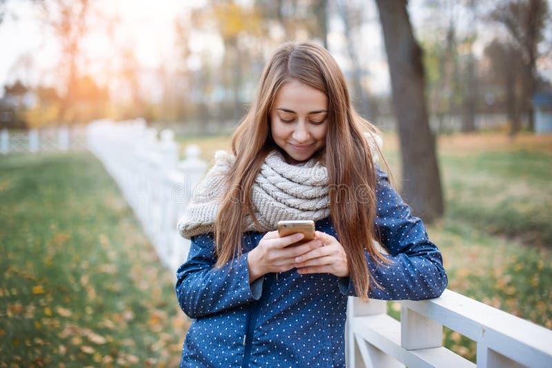 使用智能手机的愉快的年轻女人在步行期间在秋天城市公园 免版税库存图片