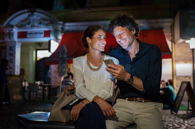 使用智能手机的愉快的成熟夫妇在晚上 免版税库存照片