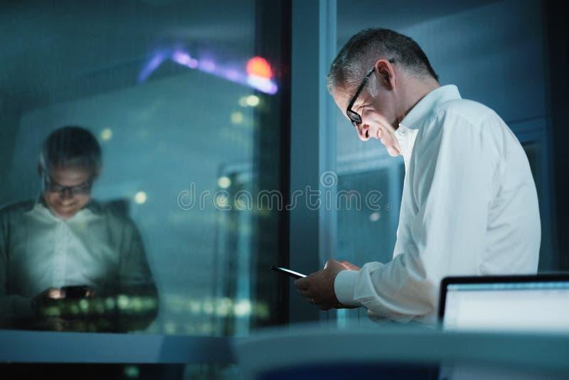 使用智能手机的愉快的经理在黑暗的办公室在晚上 免版税库存图片