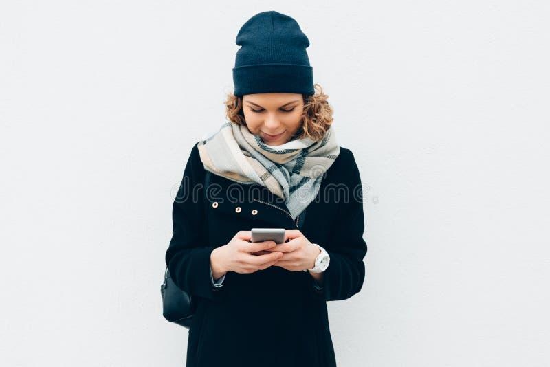 使用智能手机的愉快的行家女孩户外在墙壁附近在冬天 免版税库存照片