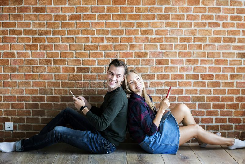 使用智能手机的愉快的逗人喜爱的年轻夫妇 免版税库存图片