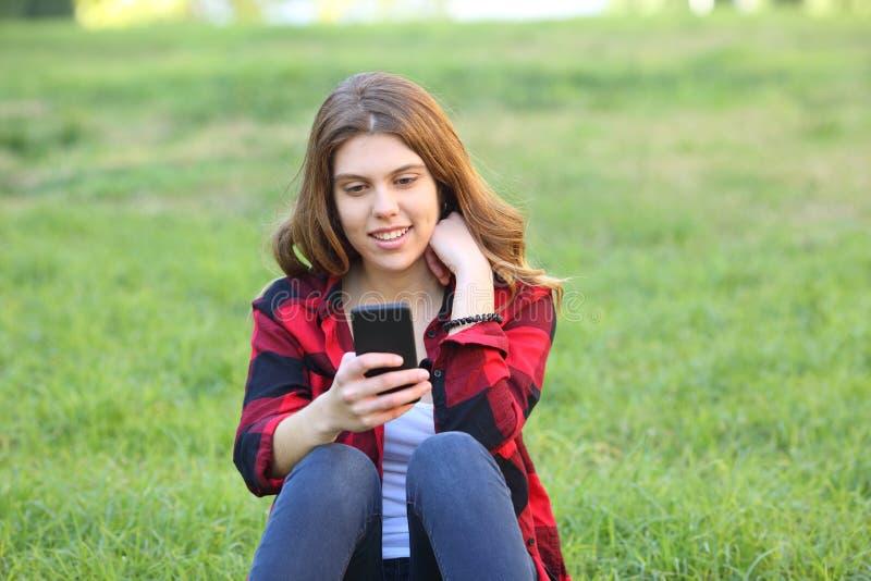 使用智能手机的愉快的青少年在草 免版税图库摄影