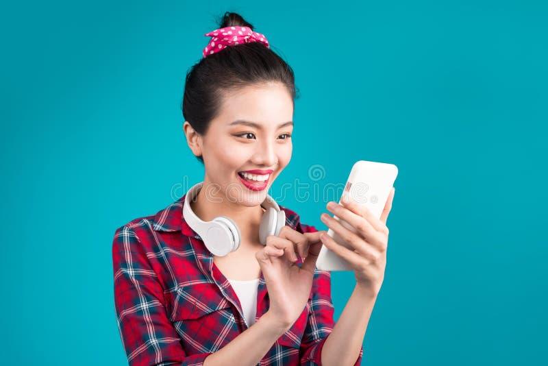 使用智能手机的愉快的年轻亚裔妇女站立在蓝色 免版税库存图片