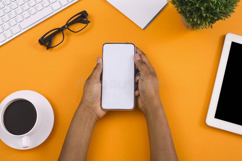 使用智能手机的手在白色木背景 库存照片