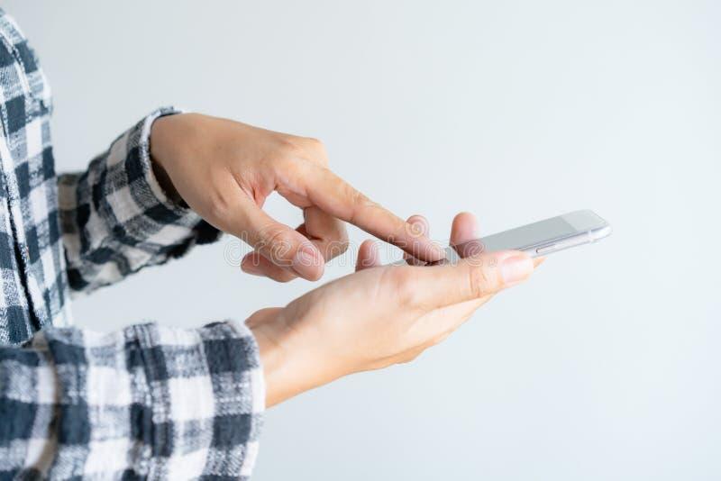 使用智能手机的接近的妇女手在白色背景 妇女屏幕的手指在手机的 免版税库存照片