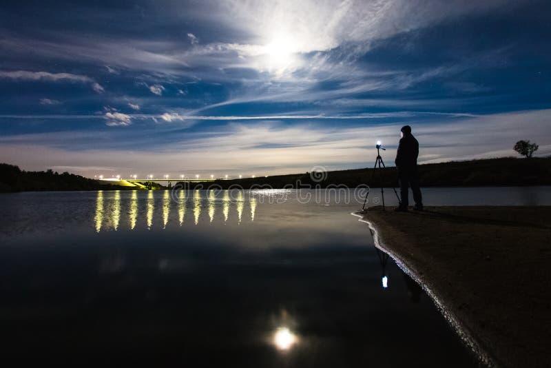 使用智能手机的摄影师对夺取美好的夜风景 库存图片