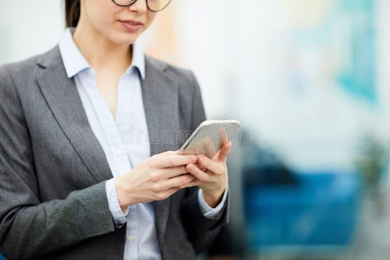 使用智能手机的无法认出的女实业家 库存照片