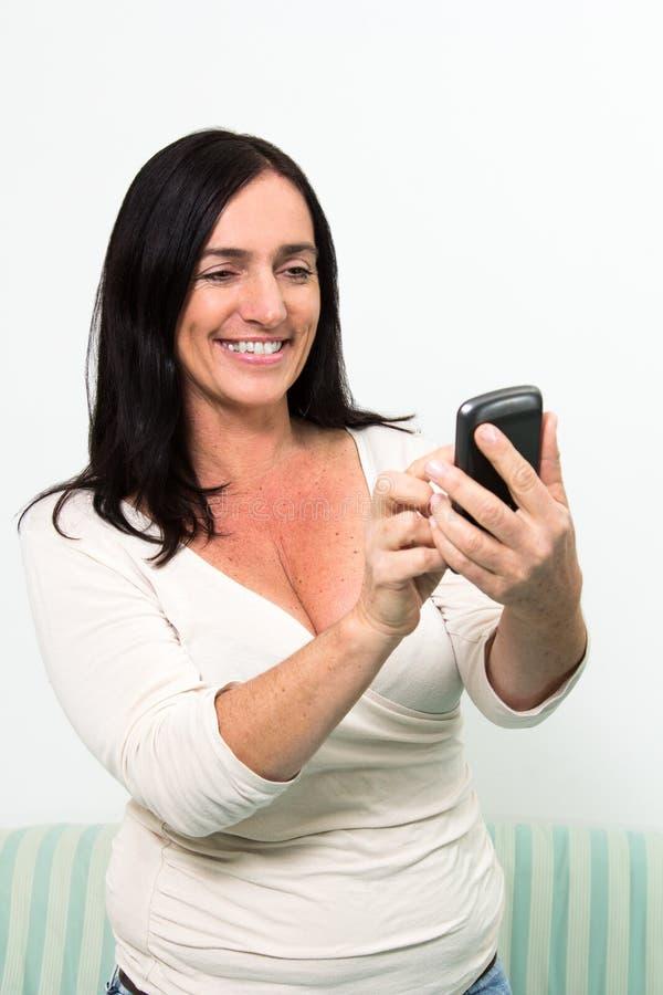 使用智能手机的深色头发的妇女 库存图片