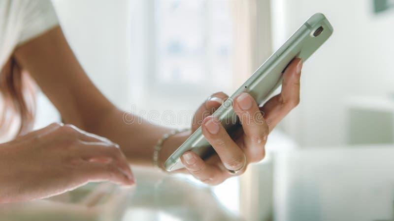 使用智能手机的特写镜头亚洲手在美丽的白色房子的玻璃桌上 免版税库存照片