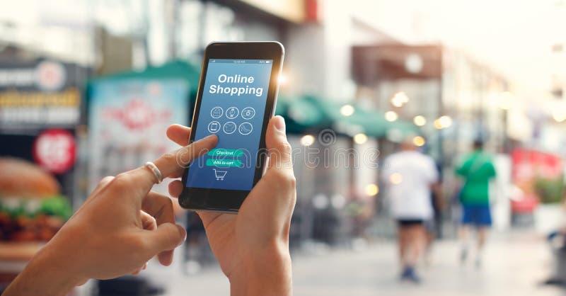 使用智能手机的男性手在街道上的网上购物的在城市 免版税图库摄影