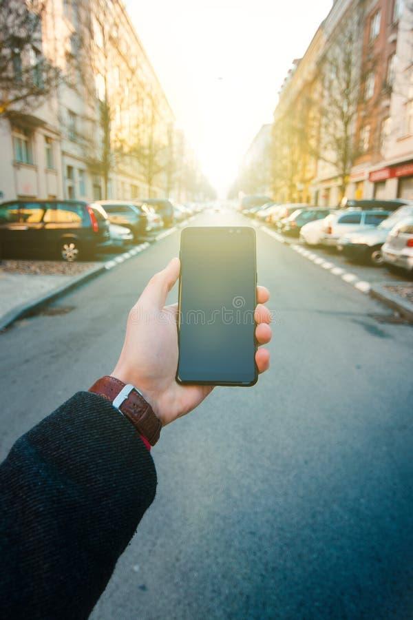 使用智能手机的男性手在街道上 技术和人脉的概念 有手表的商人,外套和采取酸碱度 免版税库存照片