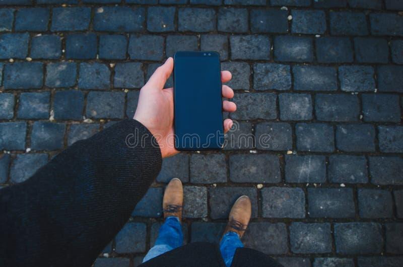 使用智能手机的男性手在街道上 技术和人脉的概念 有手表的商人,外套和采取酸碱度 库存图片