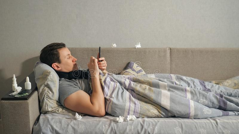 使用智能手机的病的人在沙发 库存图片