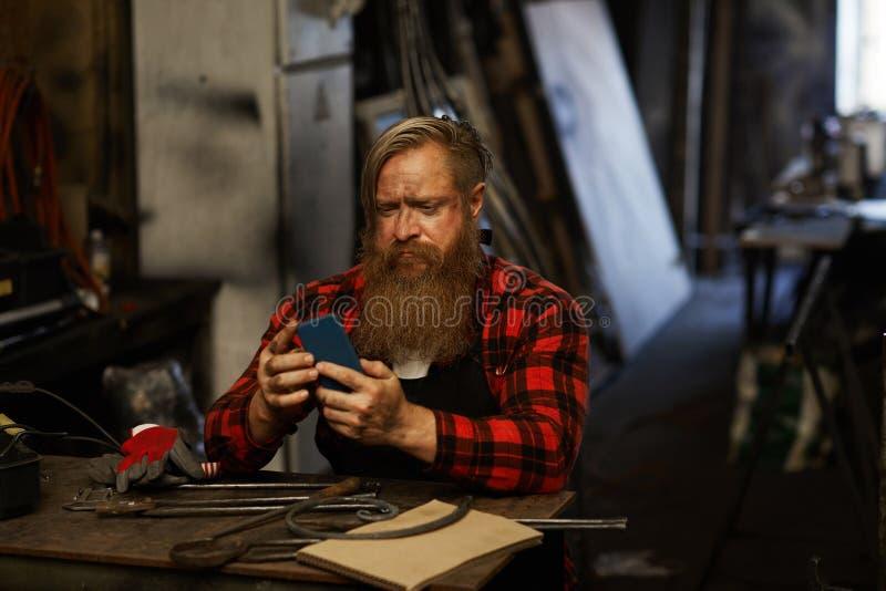 使用智能手机的皱眉的有胡子的铁匠 免版税库存图片