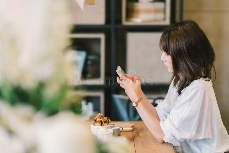 使用智能手机的美丽的亚裔女孩在咖啡馆用巧克力多士和冰淇凌 咖啡店点心和现代偶然生活方式 库存图片