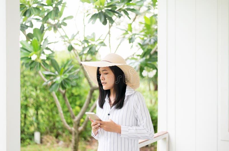 使用智能手机的美丽的亚裔妇女画象和微笑对室外,正面认为,好态度 免版税库存照片