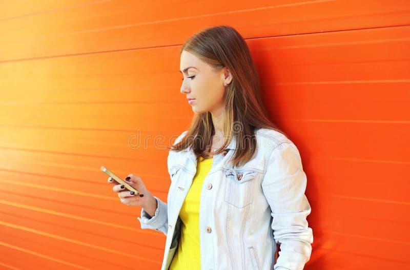 使用智能手机的美丽的女孩在五颜六色的桔子的外形 免版税库存图片
