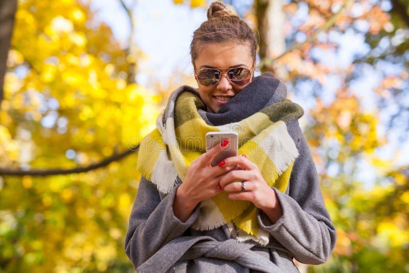使用智能手机的美丽的女孩在公园 秋天时间 库存照片