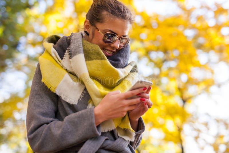 使用智能手机的美丽的女孩在公园 秋天时间 免版税库存图片