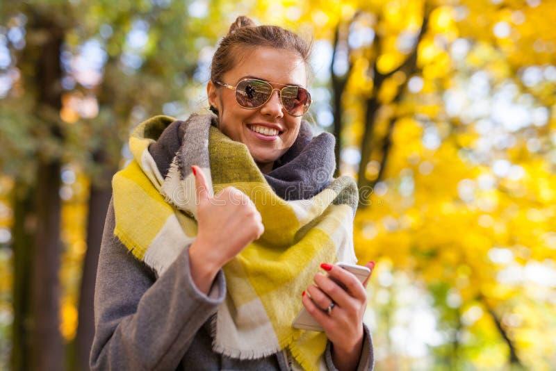 使用智能手机的美丽的女孩在公园 秋天时间 Posi 库存图片