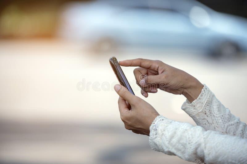 使用智能手机的美丽的妇女的手叫为与汽车问题的帮助 库存照片
